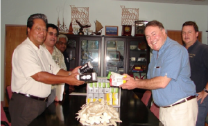 Hon. Tom Roper, GSEII Project Manager, presents President Note with 10,000 energy efficient lightbulbs from Climate Care.